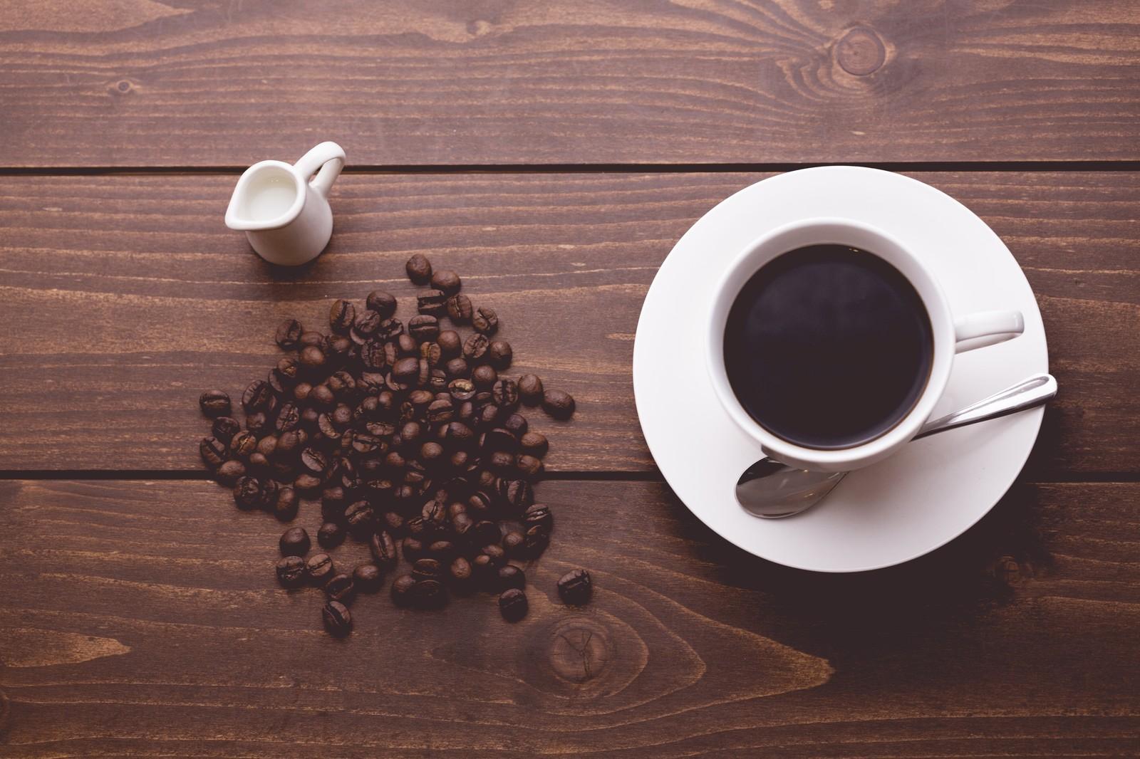 散らばるコーヒー豆と淹れたてのコーヒー